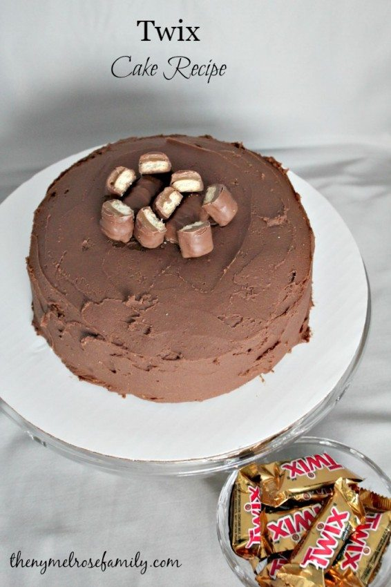 Twix Cake on a plate with a bowl of wrapped twix next to it
