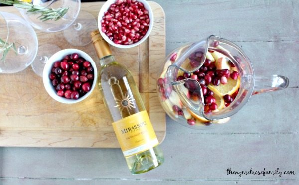 Christmas Sangria with White Wine and fruits on a table with cutting board