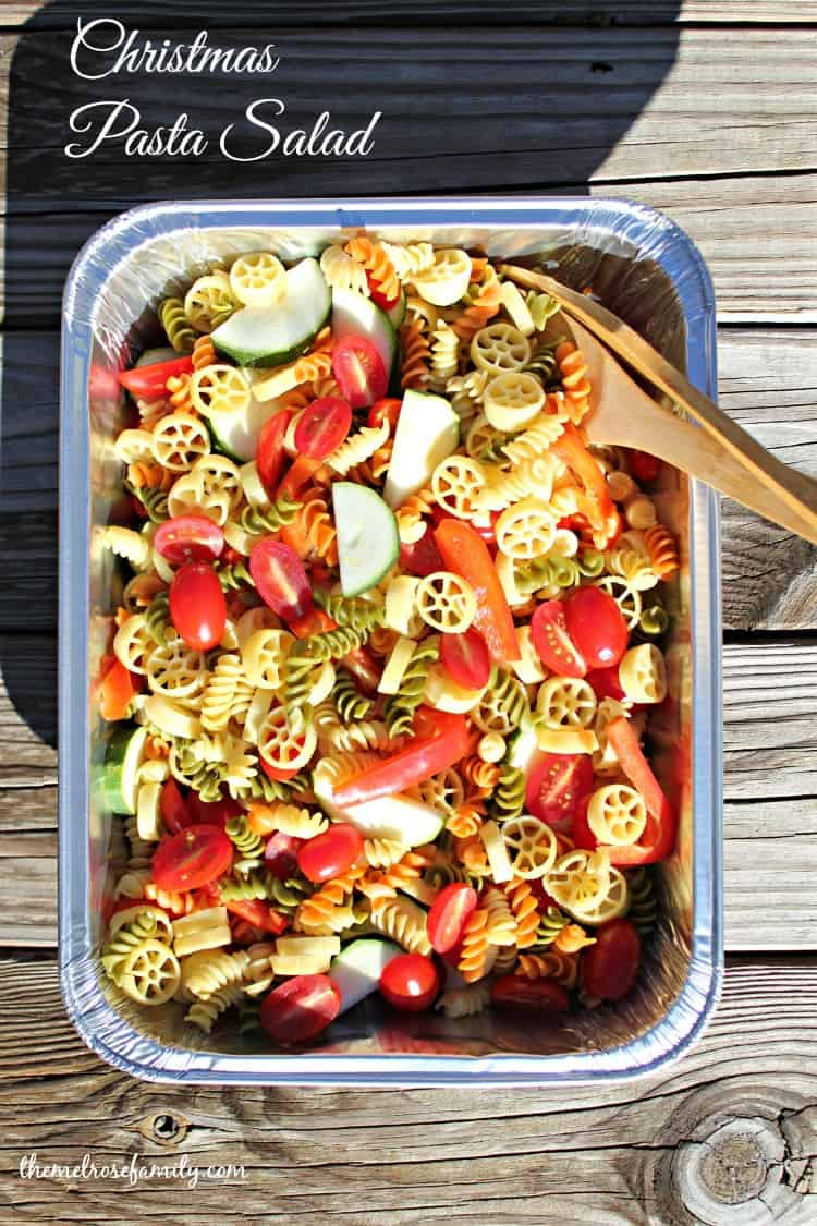 christmas pasta salad in a portable tin dish with a wooden serving spoon