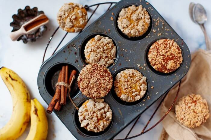 Freshly baked banana bread muffins in a pan with cinnamon sticks