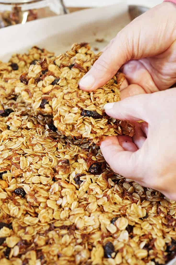 Cranberry Orange Granola being broken into pieces