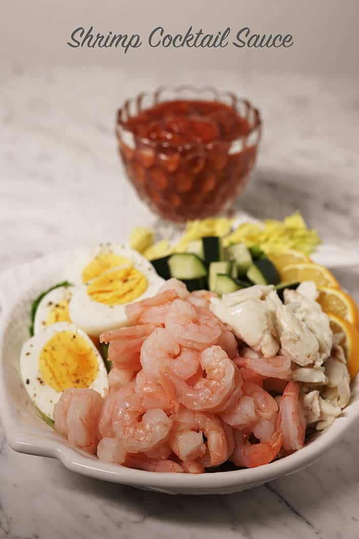 Shrimp Cocktail Sauce in a bowl with a plateful of seafood and eggs for dipping in front of it.