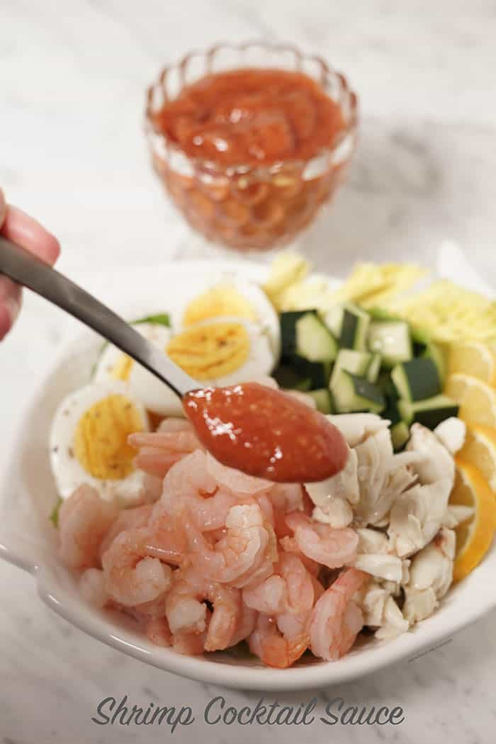 Shrimp Cocktail Sauce on a spoon held above a platter full of seafood.