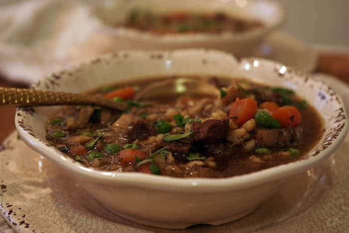 Beef Barley Soup recipe in a white bowl with a soup dipped into the bowl