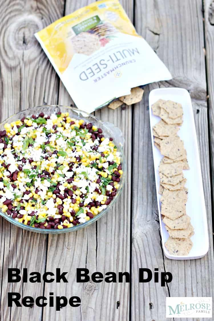 Black bean dip recipe in a glass serving dish with a serving tray full of crunchmaster crackers next to it.