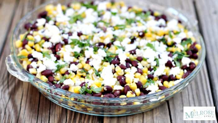 Black bean dip recipe with corn and topped with feta and parsley in a glass serving dish up close