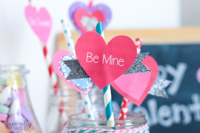 Valentine's Day party ideas of the straw topper Be Mine up close on a straw