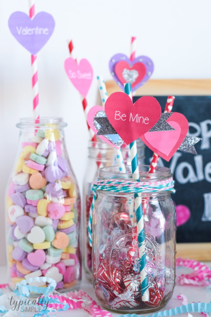 Valentine's Day party ideas of straw toppers in multiple decorative glass jars filled with candy.