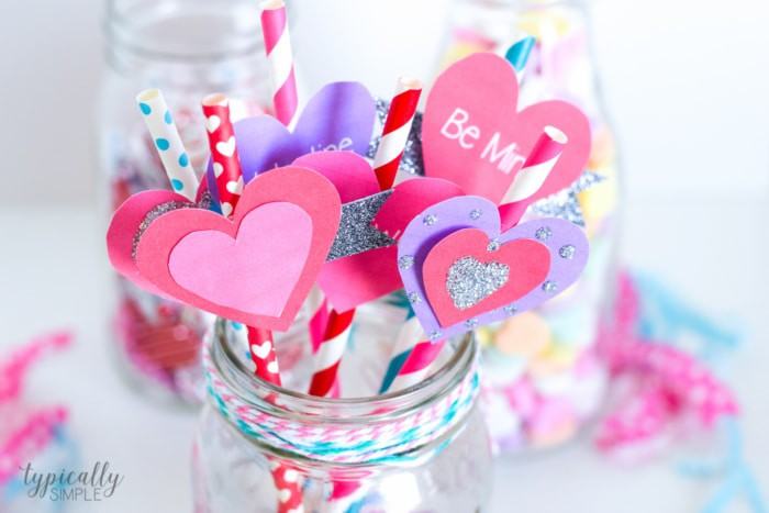 Valentine's Day Party Ideas of Straw Toppers up close sticking out of a glass mason jar with pink and blue bakers twine around the outside of the jar.