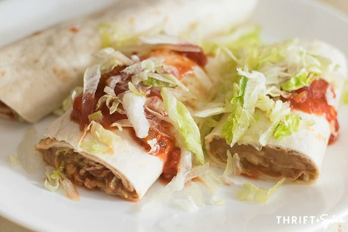 Rolled up bean burrito recipe topped with salsa and shredded lettuce on a white plate