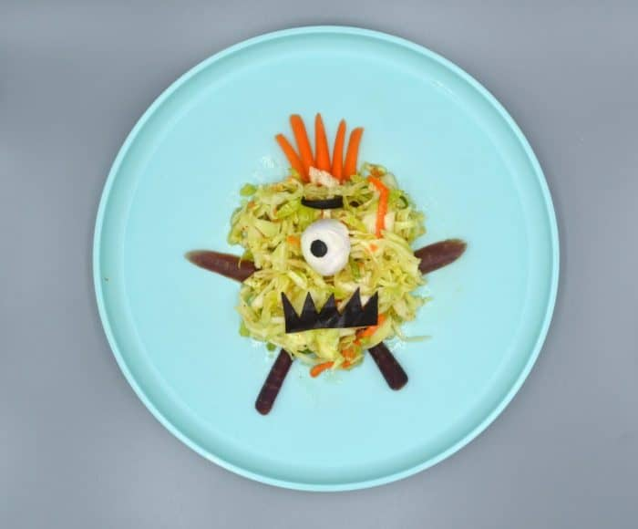 Easy coleslaw monster with carrot hairs and hard boiled egg as an eye on a blue plate