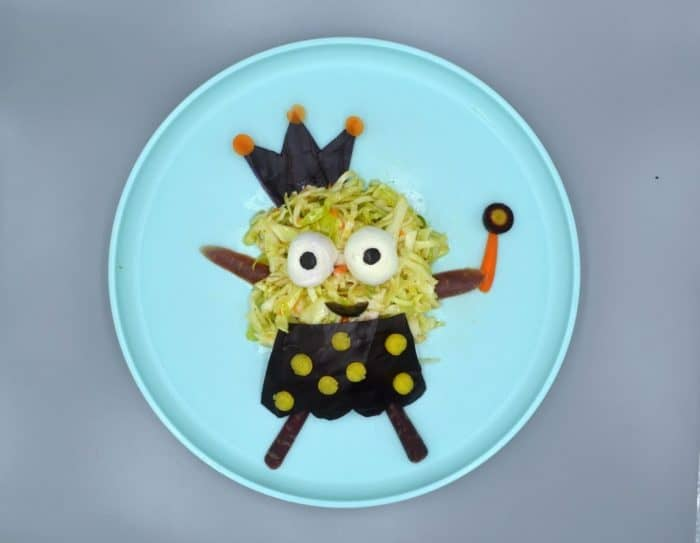 Easy coleslaw monster with a crown and wand made out of carrots on a blue plate