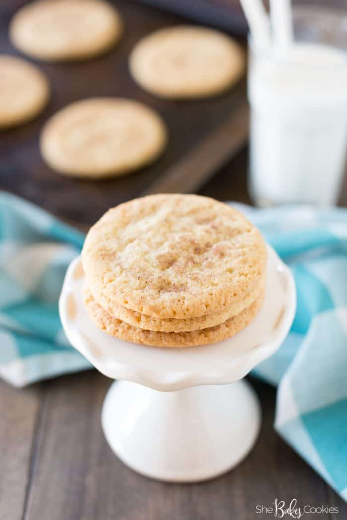 Easy snickerdoodle recipe on a white pedestal serving platter with more cookies on a baking sheet and a glass of milk in the background