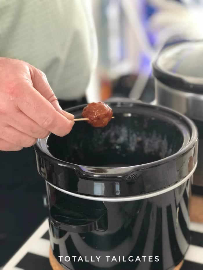 meatballs in crock pot with bourbon flavor on a toothpick held above the crock pot