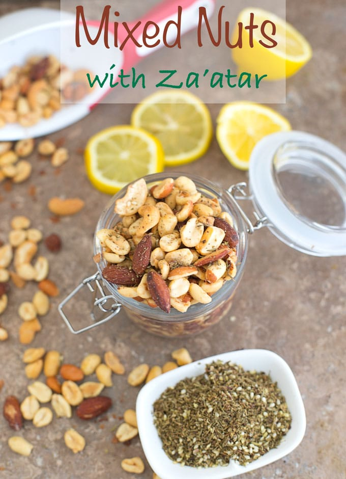 mixed nuts with za'atar in a glass jar on a counter with the za'atar spice in front of it and lemon slices behind it