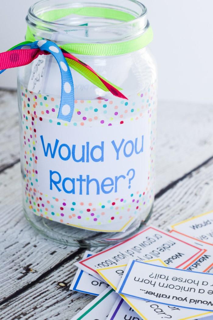 Would you rather for kids decorated glass mason jar with questions in front of it.