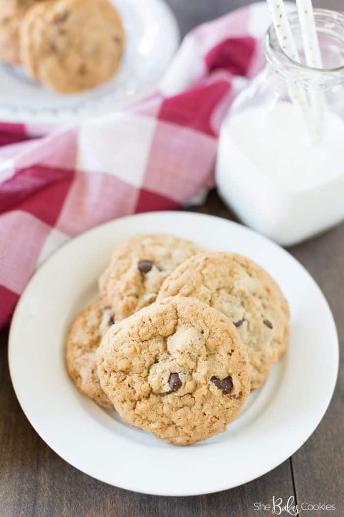 Coconut Chocolate Chips Cookies stacked on a white plate with a cup of milk in the background and a gingham red towel