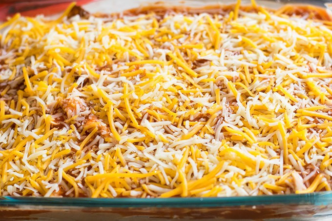 Final step of the easy chicken enchilada casserole with more beans and chicken on top of the corn tortillas with enchilada sauce and shredded cheese spread on top.