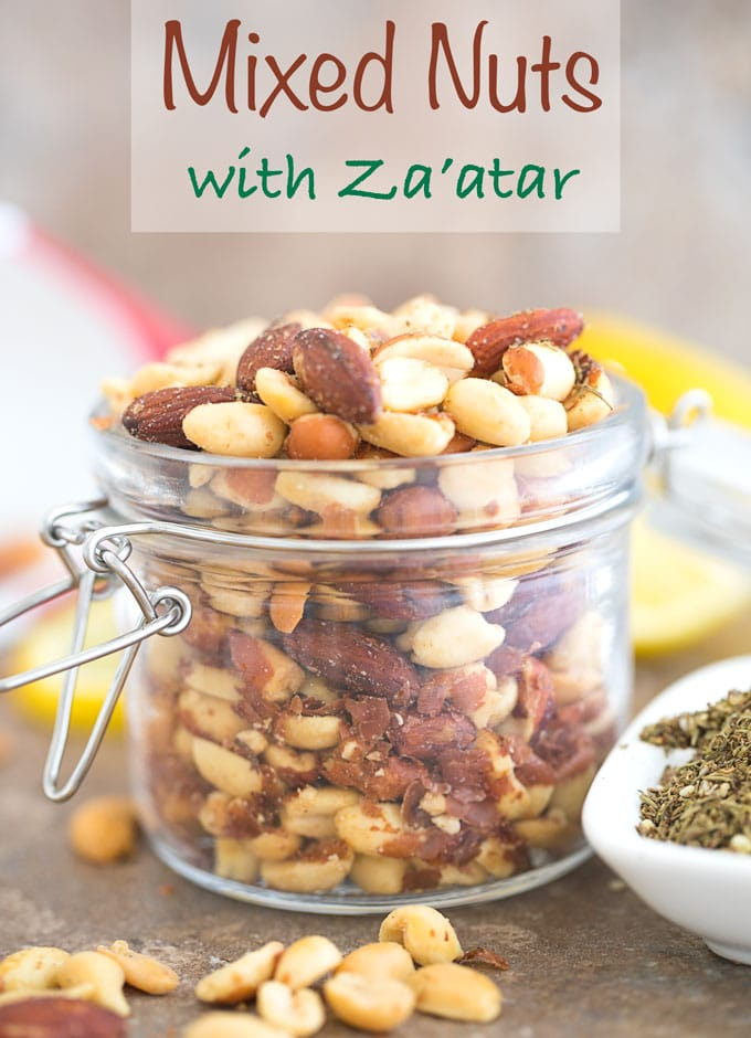 mixed nut with za'atar in a glass jar on a counter with nuts falling out