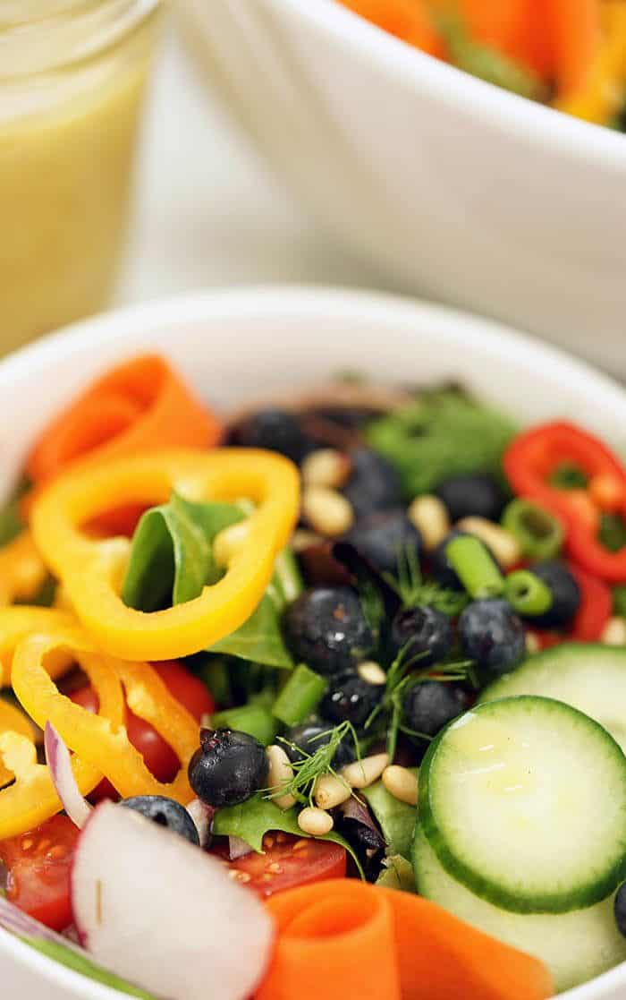 Garden salad recipe in a white bowl topped with sliced yellow peppers, cucumbers and blueberries