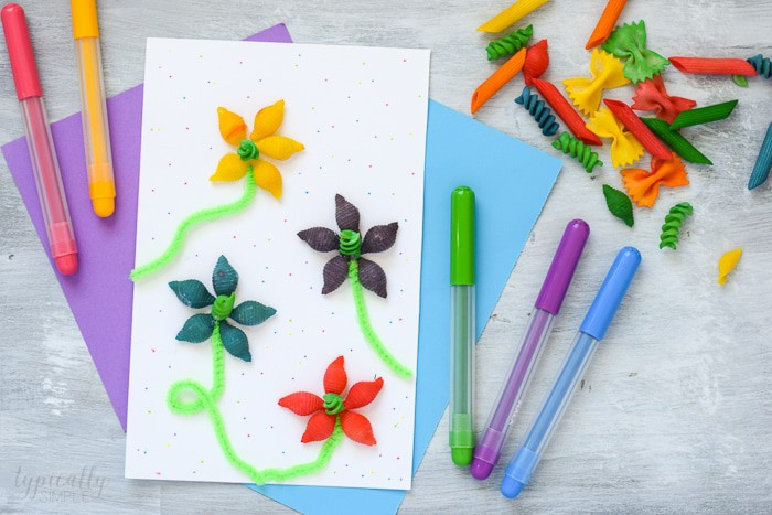 Spring Crafts for Kids with colorful pasta flowers with green stems made out of pipe cleaners on white paper with pens and pasta surrounding it.
