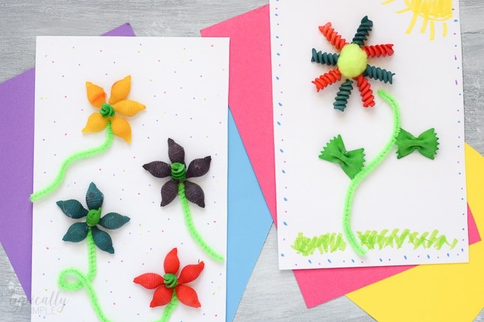 Two different masterpiece Spring Crafts for Kids of colorful pasta flowers on paper.