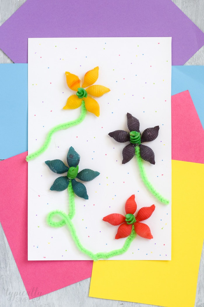 Spring Crafts for Kids of yellow, green, purple and red pasta flowers with green pipe cleaner stems on white paper