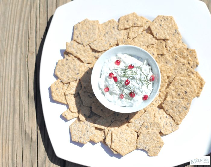 Cucumber dip recipe with feta garnished with pomegranates and fennel fronds in a white dip bowl with crunchmaster crackers surrounding it on a white serving platter.
