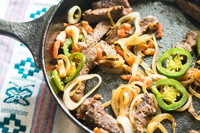 Steak fajitas recipe in a skillet cooking with onions, jalapenos and red peppers.