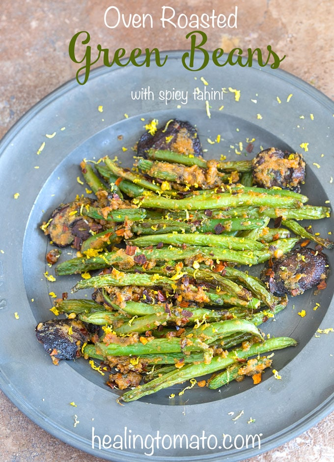 oven roasted green beans with spicy tahini and mushrooms on a blue plate photographed from above