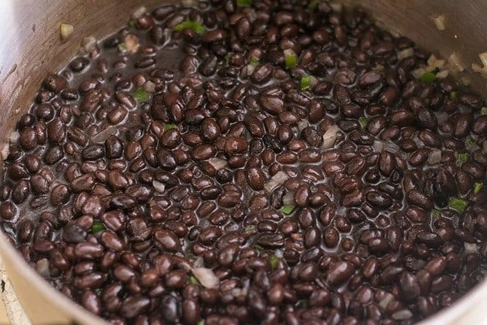 Black beans in a large pot with the sauteed jalapeno and onion for the black bean dip recipe