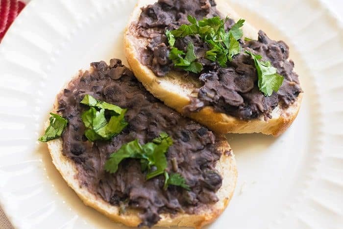 Black bean dip recipe on flatbread topped with cilantro