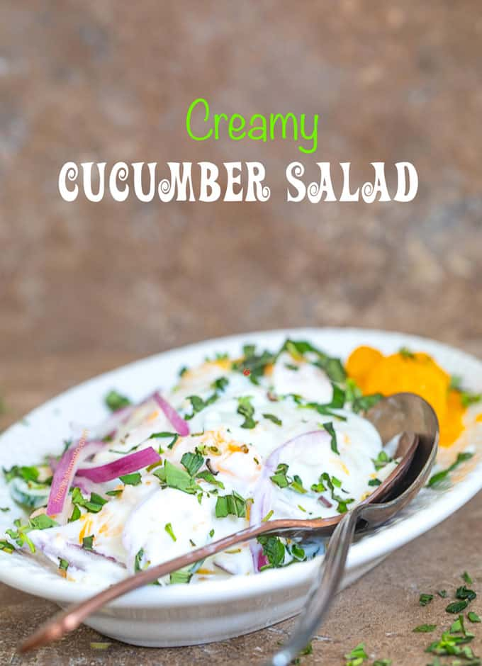 Creamy Cucumber Salad topped with red onions, mandarin oranges and tarragon and oregano on a white serving dish
