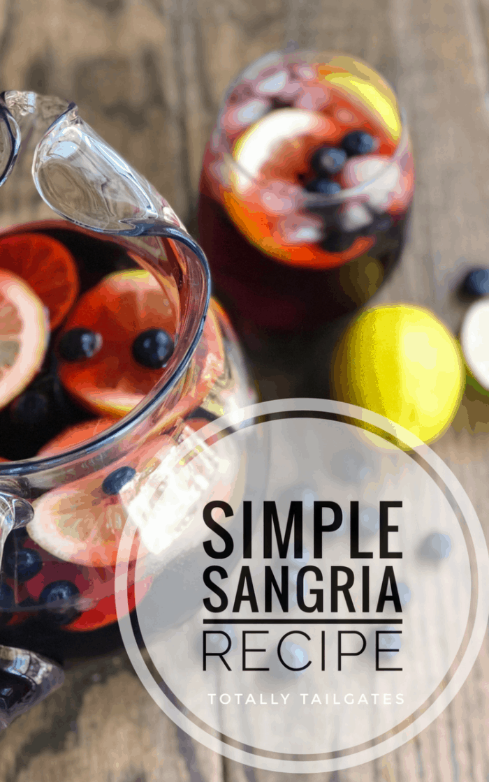 Simple sangria recipe in a pitcher with a glass of it beside it on a wooden table.