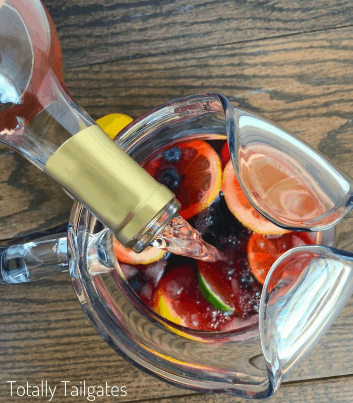 Simple Sangria recipe being made inside of a large pitcher with fruit already in the pitcher and the wine being poured in