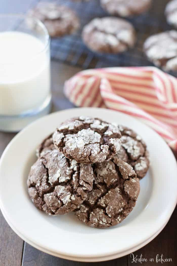 Chocolate Crinkle cookies recipe on a white plate with a glass of milk in the background