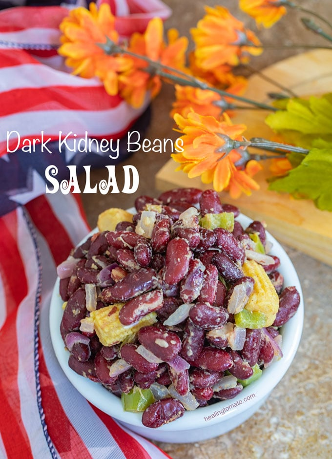 Dark Kidney Beans Salad with baby corns in a white bowl on a counter with orange flowers in the background