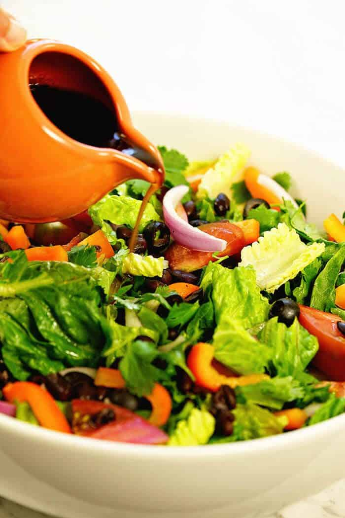 Southwest salad recipe in a white bowl with balsamic dressing being poured on it