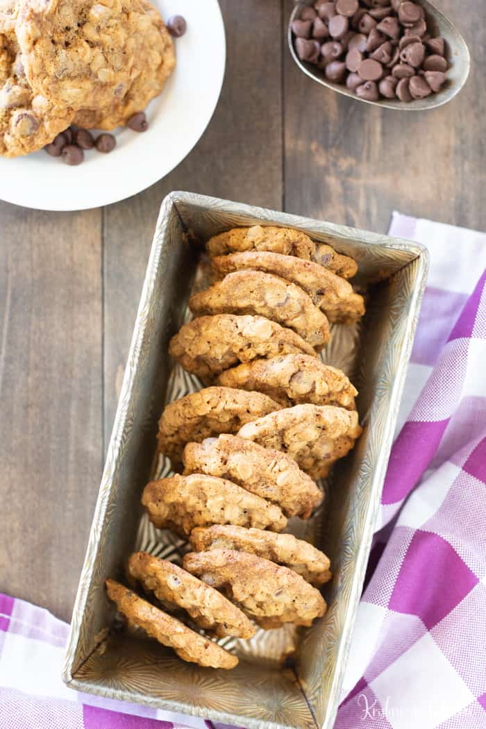 The best oatmeal chocolate chip cookies in a cookie tin on a table with a purple gingham towel