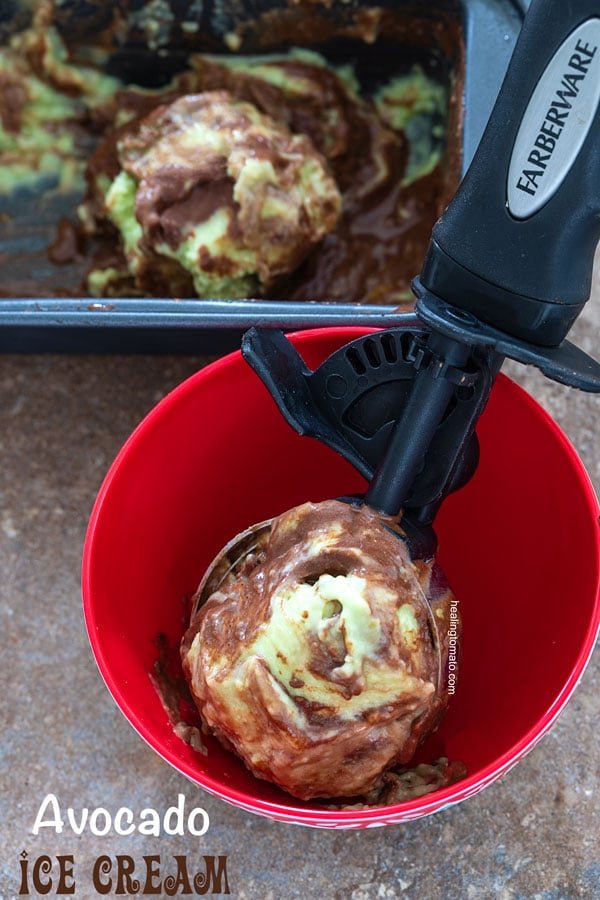 Avocado ice cream in an ice cream scooper placed in a red bowl
