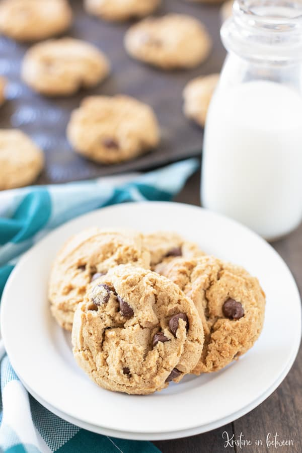 four chocolate chip peanut butter cookies on a plate with a glass of milk