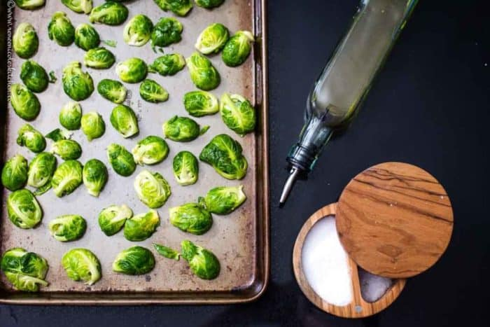 brussels sprouts on a sheet pan with oil and salt in the background