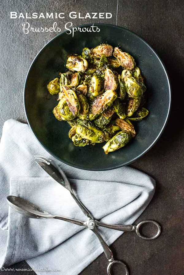 roasted brussels in a black bowl with a napkin and metal tongs
