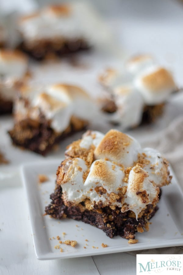 S'more brownies on a plate with more brownies behind it