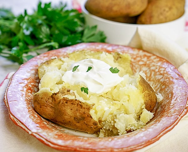 pressure cooker baked potato on plate with sourcream