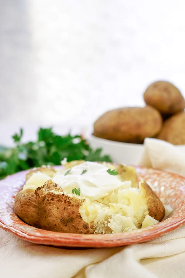pressure cooker baked potato on a plate with a bowl of potatoes behind it