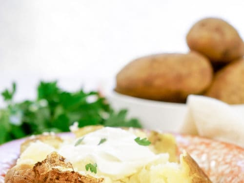 baked potato on a plate loaded with sour cream