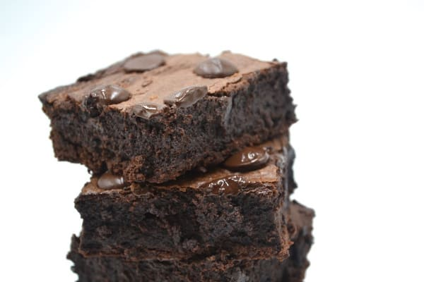 fudgy brownies stacked three tall with a white background