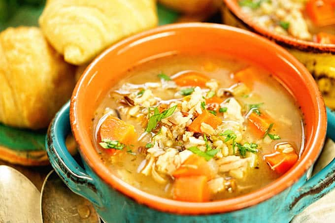 Wildrice and leftover turkey soup with carrots in a teal and orange stoneware bowl with dinner rolls laying behind it