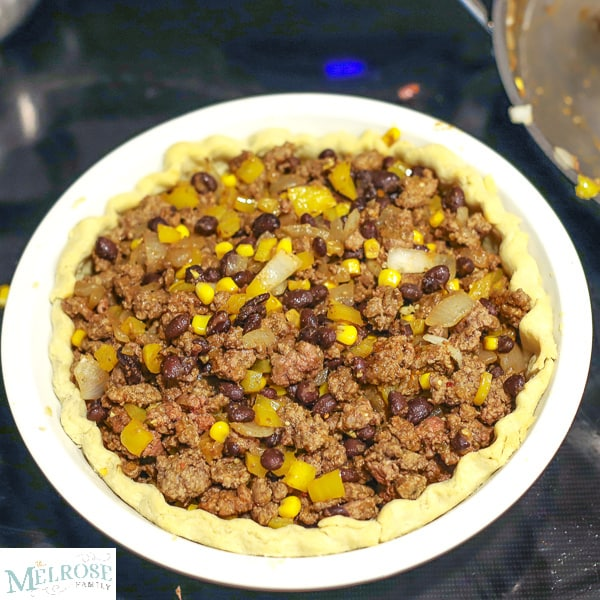 Taco pie filling - ground beef, corn, onions, peppers, beans and seasonings in a pie crust sitting on top of the oven.